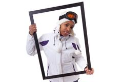 Young black woman in ski clothes holding a picture frame Stock Photos