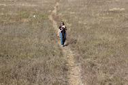 Stock Photo of Mom walking down grass hill with child in a carrier