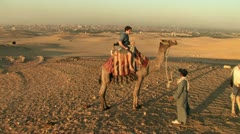 Young Man dismounts a Camel Stock Footage