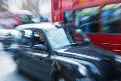 motion blur picture of black cab and red double decker bus in the heart of lo - stock photo