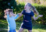 Kids playing with bubbles Stock Photos