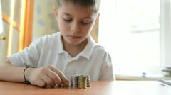 Child builds columns from coins. Dolly shot - stock footage