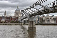 city of london, millennium bridge and st. paul's cathedral on a overcast autu - stock photo