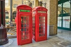 classic red telephone booth on a street of london - stock photo