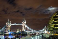 city hall on the banks of the thames with tower bridge at night, london - uk - stock photo