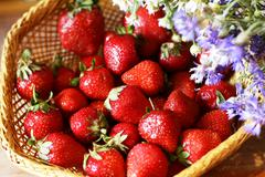 Basket of strawberries and wildflowers - stock photo