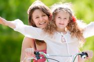 Stock Photo of young mother and her daughter on bicycle