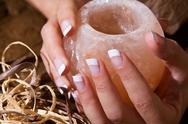 Woman's hand with french manicure holding exotic salt-crystal candlestick Stock Photos