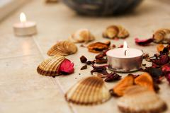 spa center, candle, mussels and rose leafs. for spa designs. - stock photo
