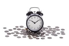 Alarm clock on a pile of coins isolated Stock Photos