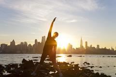 Woman runner yoga stretching manhattan skyline sunrise new york city Stock Photos