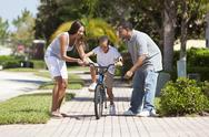 Stock Photo of african american family with boy riding bike & happy parents