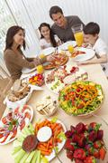 parents children family eating pizza & salad at dining table - stock photo