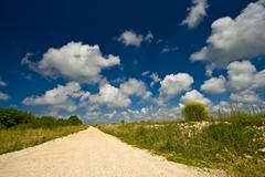 Dusty road through the field under the clouds - stock photo