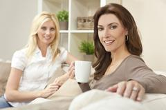 two beautiful women friends drinking tea or coffee at home - stock photo