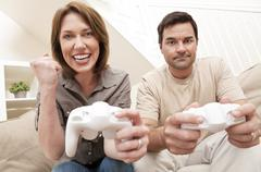 Man woman couple playing video console game Stock Photos