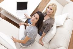 two young women using laptop computer at home on sofa - stock photo