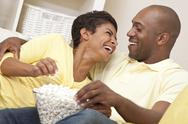 Stock Photo of happy african american couple eating popcorn watching movie at home