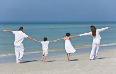 mother, father and children family holding hands at beach - stock photo