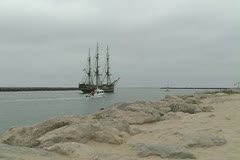 Zoom into HMS Bounty sailing up channel Stock Footage