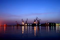 Port of Pula with shipyard cranes in the dusk with the lights Stock Photos