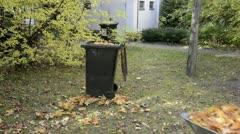 Man with wheelbarrow puts leaves in garbage bin Stock Footage