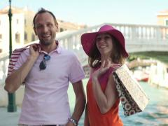 Happy rich couple with shoping bags in Venice, crane shot NTSC - stock footage