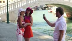 Stranger taking photo of girlfriends with cellphone in Venice, crane shot HD Stock Footage