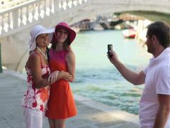 Stranger taking photo of girlfriends with cellphone in Venice, crane shot NTSC Stock Footage