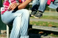 Mother with son sitting on bench in the park, steadycam shot Stock Footage