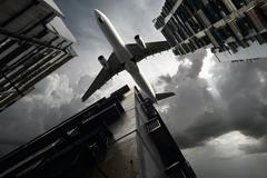 aeroplane flying over hong kong housing - stock photo