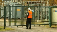 Engineer with folder near the electricity substation Stock Footage
