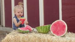 Toddler grabs watermelon slice Stock Footage