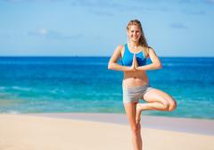 beautiful woman practicing yoga on the beach in hawaii - stock photo