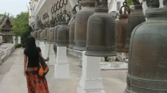 Thai woman ringing  big bells at a buddhist temple Stock Footage