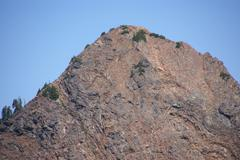 exposed steep rocky face of red mountain - stock photo
