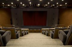 A stage of a auditorium with a closed curtain Stock Photos