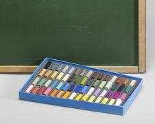 Blackboard edge and crayons Stock Photos