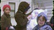 Stock Video Footage of KIDS BUILD SNOWMAN Xmas Children Winter Fun 1960s Vintage Film Home Movie 5517