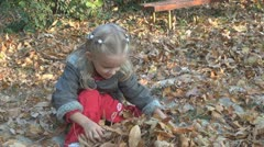Child Playing with Dried Leaves, Little Girl Throwing Autumn Leaves in the Air - stock footage