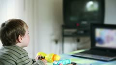 Little boy watching cartoons at laptop and eating apples Stock Footage