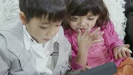 Cute young children are playing on a tablet computer Stock Footage