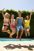 Friends jumping together near swimming pool Stock Photos
