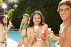 Girls eating ice cream cones near swimming pool Stock Photos