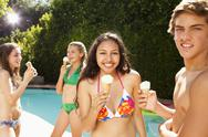 Stock Photo of Girls eating ice cream cones near swimming pool