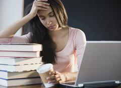 Tired Hispanic teenager holding coffee cup Stock Photos