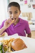 Hispanic boy eating hamburger and french fries Stock Photos