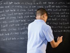 Hispanic boy writing punishment on blackboard Stock Photos