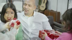 Two children giving their father brightly wrapped gifts Stock Footage