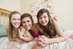 Smiling Caucasian teenage girls in bedroom - stock photo